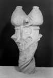 Foliated terminal of a Roman shaft: above a series of carved spirals terminating in acanthus leaves are two stylised pine cones flanked by a foliate scroll. The tops of the pine cones are smoothed forming flat surfaces.