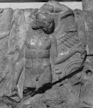Fragment of a cresting plaque from the ridge of a Roman roof: Eros standing amongst stylised acanthus foliage and vine tendrils