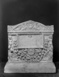 Cinerarium with <i>Genii </i>at the corners holding a garland, name plate with medallion portrait below it, and separate lid.