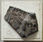 Fragment of a relief slab depicting Victory sacrificing a bull.  Only the lower part of the head and face, the body to below the waist, part of the right arm and right wing remain.
