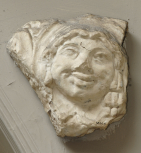 Archaistic male mask-head, part of a panel or border of scroll ornament(?)