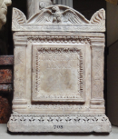 Roman cinerarium and lid: between double fillet and compressed waterleaf mouldings is a large name plate with similar borders flanked by two enriched Tuscan pilasters. The lid has a curved pediment ornamented with an eagle with wings half spread and an antefix on each of the four corners with enriched borders below on three sides. There are large palmettes carved on the ends / sides of the cinerarium.
