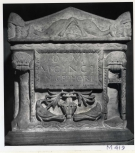 A Roman funerary urn (cinerarium) with separate lid, its name plate flanked by tripods.