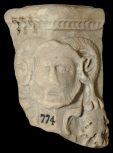 Corner of a Roman funerary (cinerary) urn with an ammon head and garland