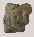 Fragment of a Roman sarcophagus front with a medallion mask and figure of Eros.