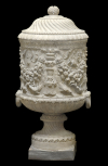 Cinerary vase with decorative handles and the body carved with candelabra(?) and garlands.