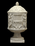Round cinerary urn carved with genii and sphinxes.