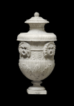 Roman funerary (cinerary) vase decorated with masks and a palmette frieze.
