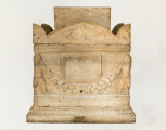 Roman garlanded funerary urn (cinerarium) with genii figures at the front corners and a separate lid