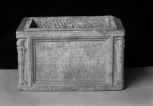A Roman funerary urn (cinerarium) with a rectangular name plate between lighted torches