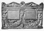 A Roman double funerary urn (cinerarium) and lid, carved with garlands held up by bukrania and dolphins at the lower front corners.