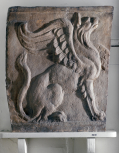 An end panel from a Roman sarcophagus carved wtih a Griffin in relief